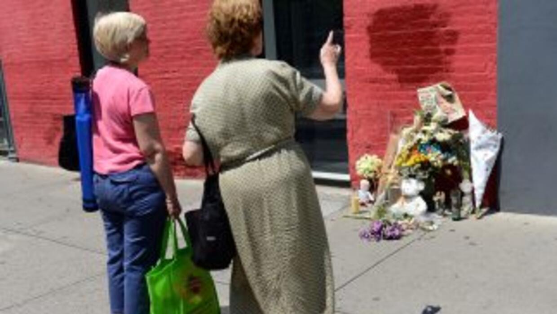 Dos mujeres en Nueva York miran un altar en memoria de Etan Patz, desapa...