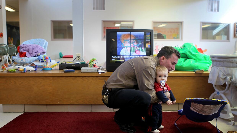 El oficial John MacIntosh sostiene a un bebé.