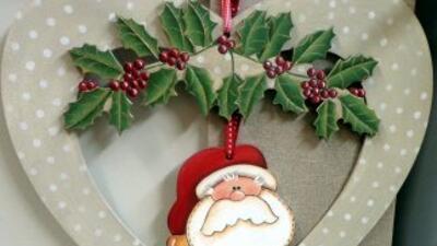 E la imagen un corazón decorado con hojas de acebo con la imagen de Sant...