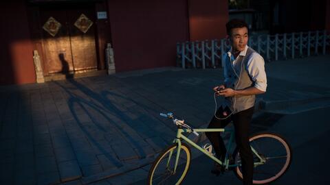 Un ciclista mira la puesta de sol en Pekín, en septiembre de 2016.