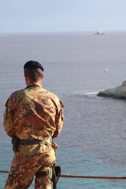Un militar italiano vigila la costa de Lampedusa, Italia. La búsq...