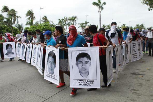 Estudiantes encapuchados con las fotos de sus 43 compañeros desaparecido...