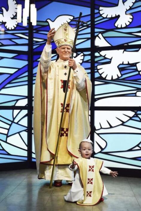 Un niño disfrazado de papa juega ante la figura de cera de Juan Pablo II...