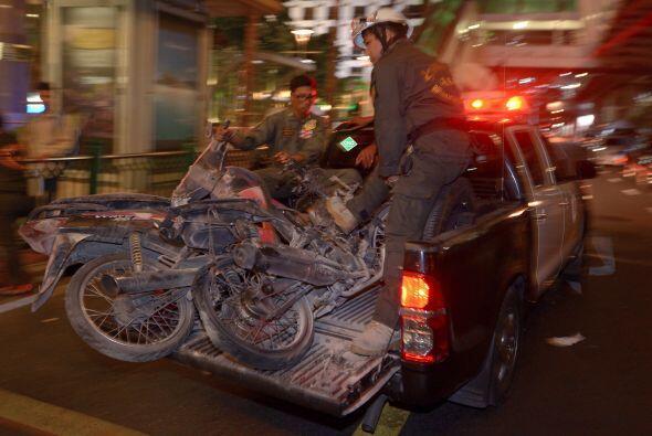 Trabajadores transportan motocicletas destruidas por la detonación.