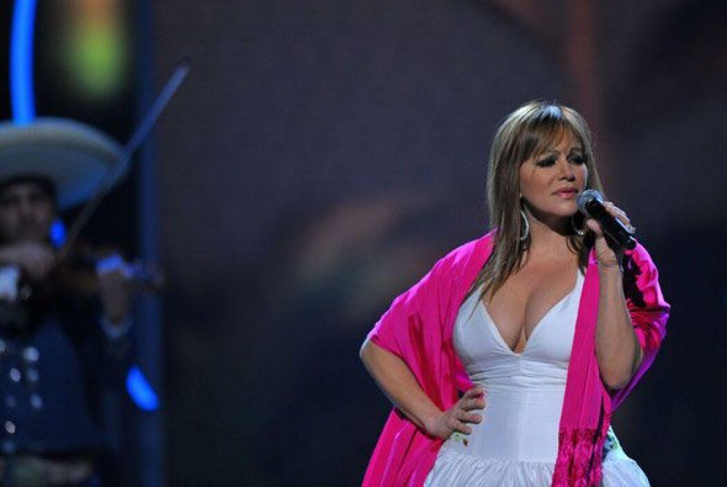 Jenni Rivera subió al escenario enfundada en un vestido blanco con rosas...
