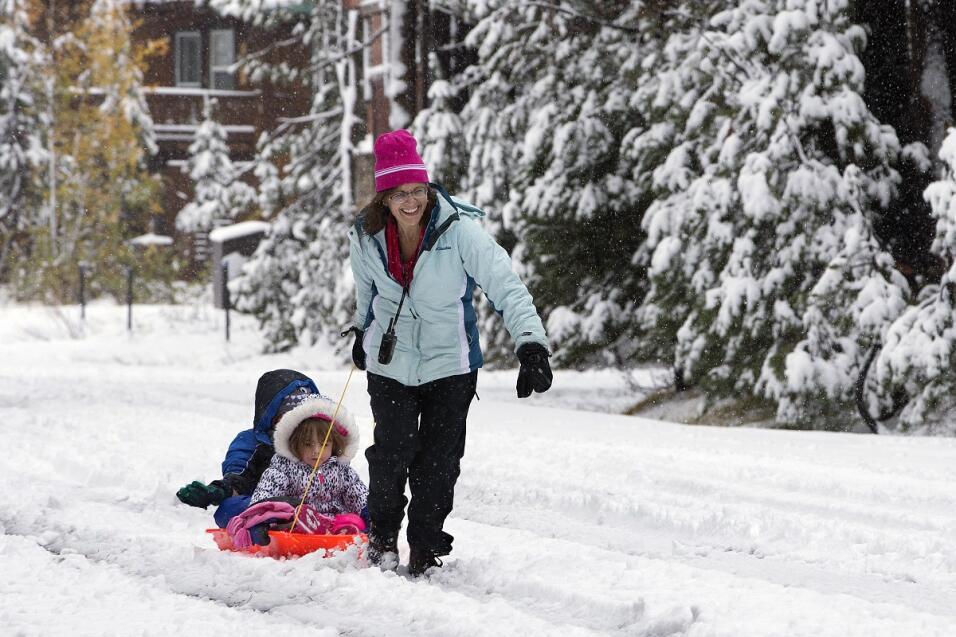 Una madre y sus hijas juegan con la nieve en Serene Lakes, CA.