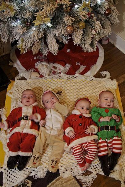 Al pie del árbol de Navidad ellos lucen como cuatro hermosos regalos de...