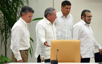 El presidente colombiano, Juan Manuel Santos, y el jefe de las FARC, Tim...