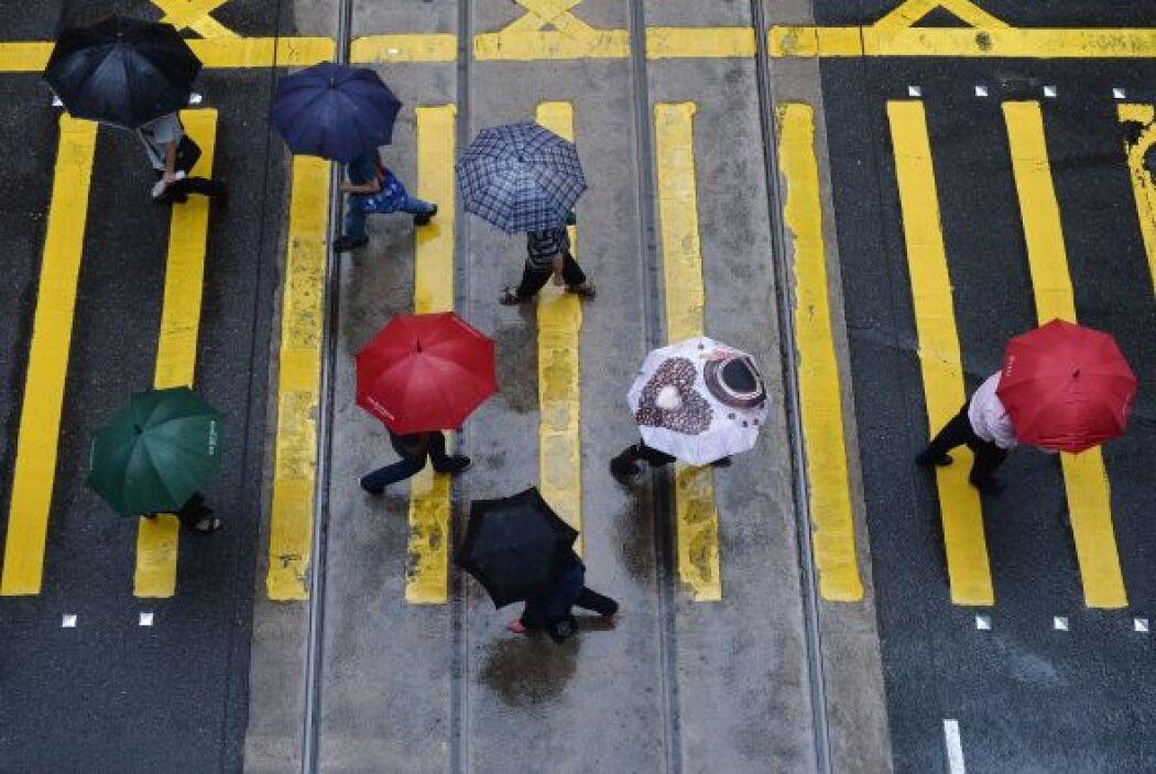 Transeúntes se protegen de la lluvia con sombrillas en una calle de Hong...