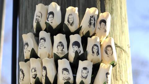 En las flores, los rostros de los 26 niños y adultos que murieron tras e...