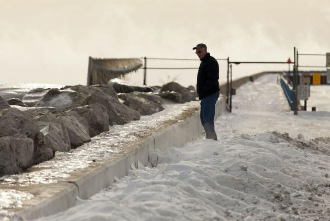 Un hombre desafía el frío y pasea por la orilla del lago Michigan, donde...
