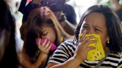 Mujeres lloran en las afueras de la fábrica de zapatos en Valenzuela, Fi...