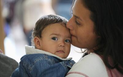Una madre indocumentada centroamericana besa a su pequeño hijo tras ser...