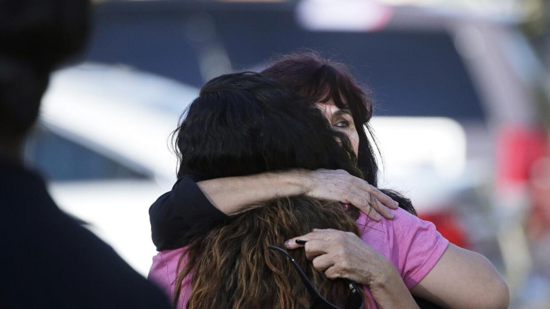 Teresa Hernández es reconfortada por una mujer en San Bernardino.