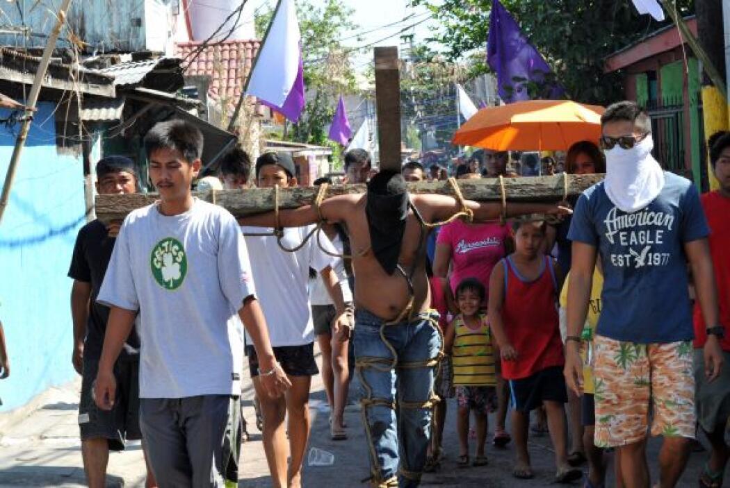 Un penitente lleva la cruz en la simbólica ceremonia.