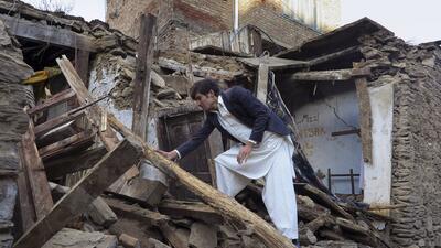 Un paquistaní examina una casa dañada por un gran terremot...