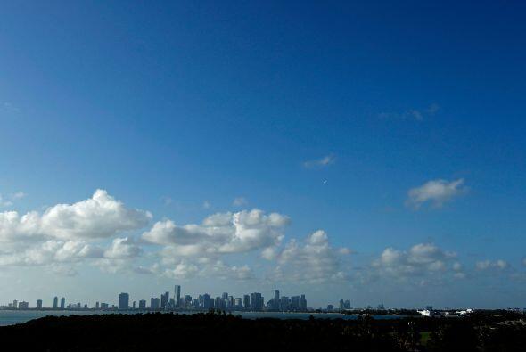 Entre nubes gigantes, un cielo azul cubre una línea de edificios...