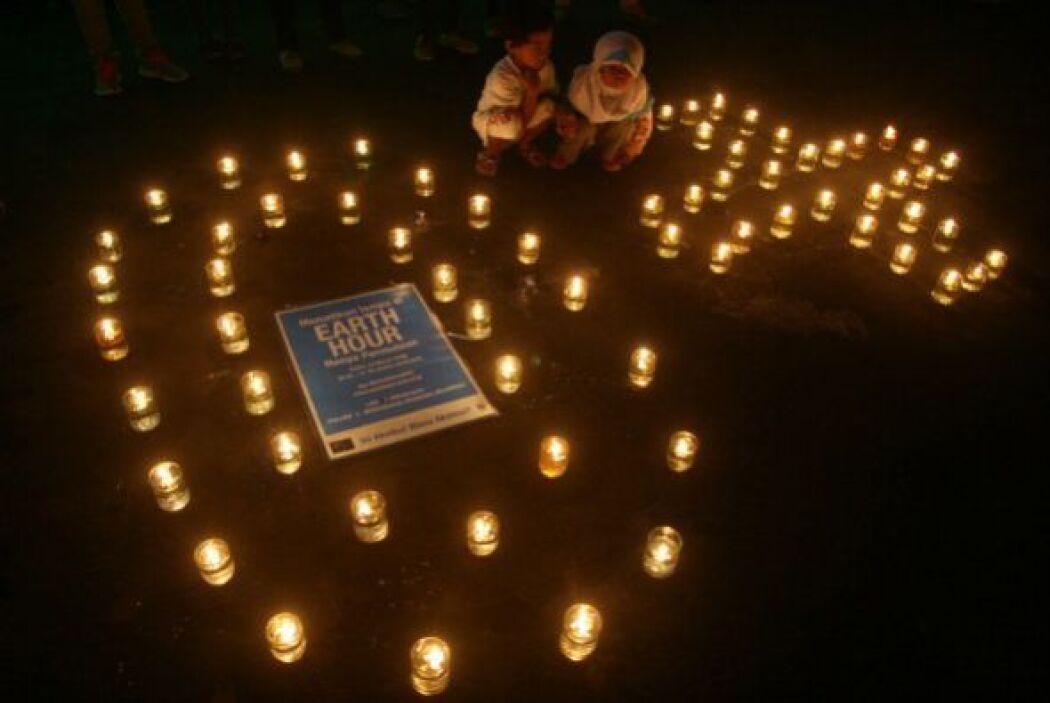 Estos niños se sientan junto a unas velas encendidas también en Java Ori...
