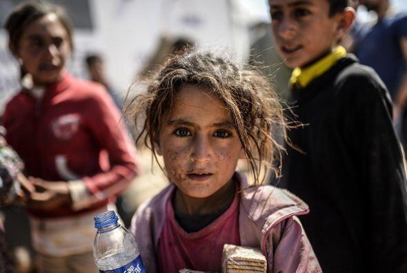 Una niña sostiene una botella de agua y un paquete de galletas. Su cara...