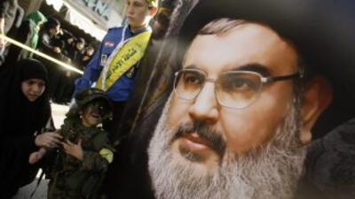 Un niño mira a un cartel con la cara de Hassan Nasrallah en Líbano