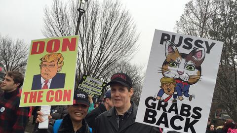 Un hombre y una mujer protestan contra Trump.
