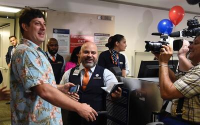 Un pasajero originario de Nueva York enseña su pasaporte antes de...