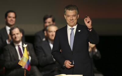 Colombia's President Juan Manuel Santos prepares to sign a modified peac...