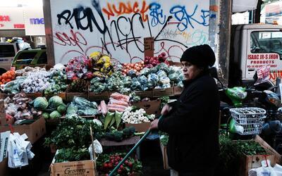 Una mujer vende vegetales en el área de Jackson Heights, Queens q...
