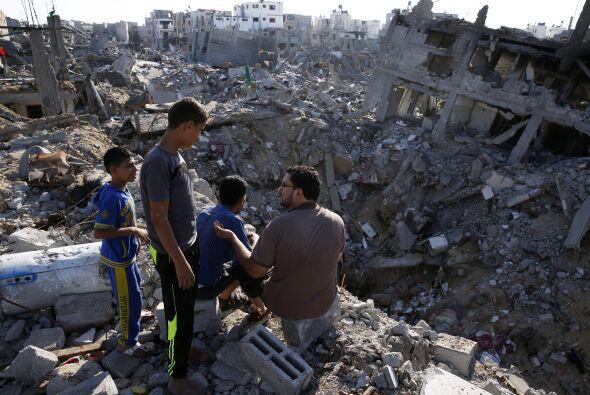 Un palestino y sus tres hijos se sientan en la azotea de su casa parcial...