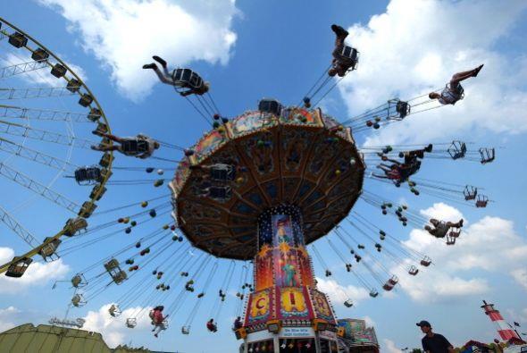 La gente disfruta de una carrusel en la feria anual Cranger Kirmes en Al...