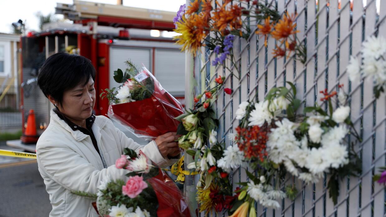 Una mujer pone flores en homenaje de las víctimas del incendio en Oaklan...