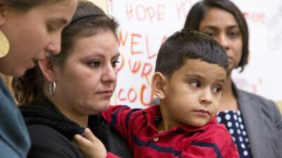 Una mujer centroamericana y su hijo en la conferencia de prensa.