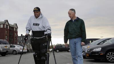 El veterano paralizado estadounidense Gene Laureano sonríe mientras camina.