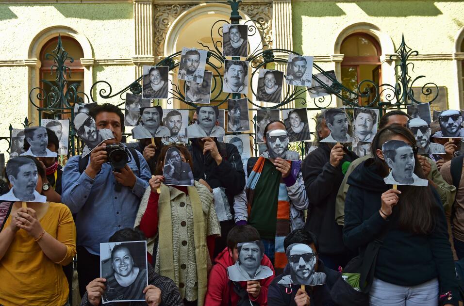 Periodistas mexicanos posan con imágenes de periodistas muertos a las pu...