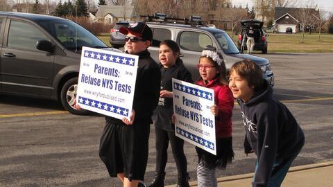 Estudiantes cargan pancartas que expresan oposición a las pruebas del es...