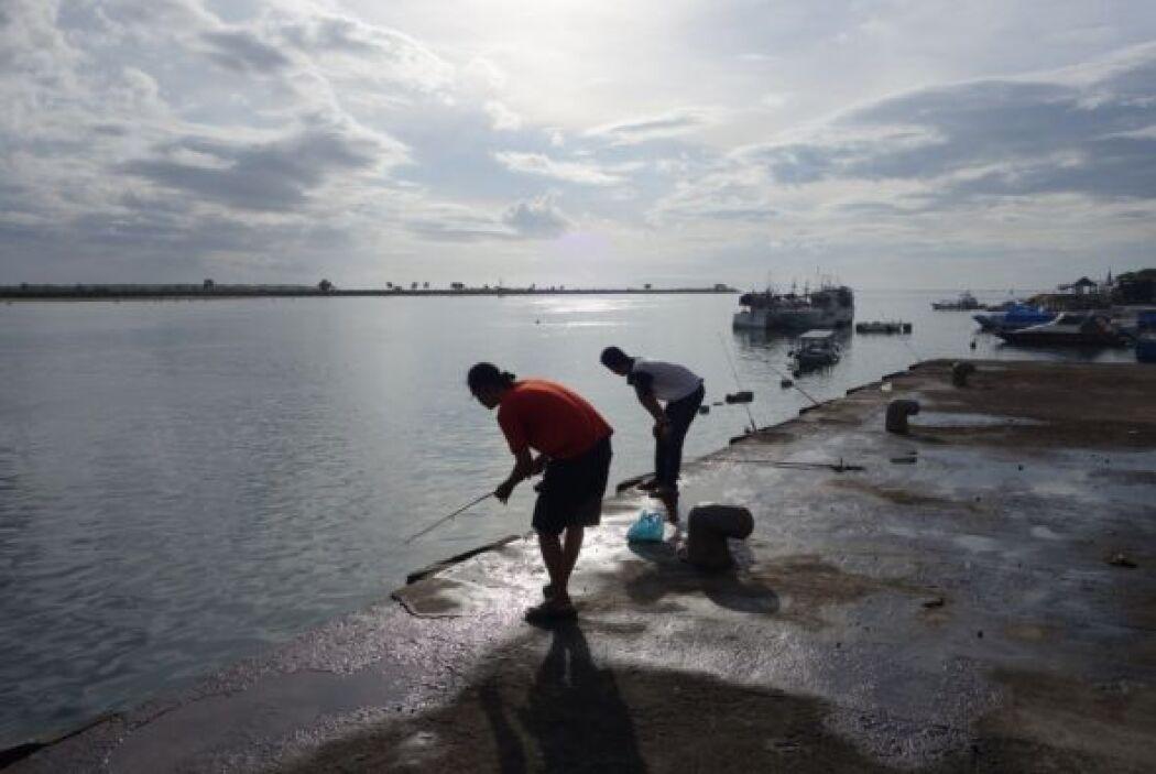 Aquí podemos ver cómo se reúne la gente para pescar a las orillas del mar.