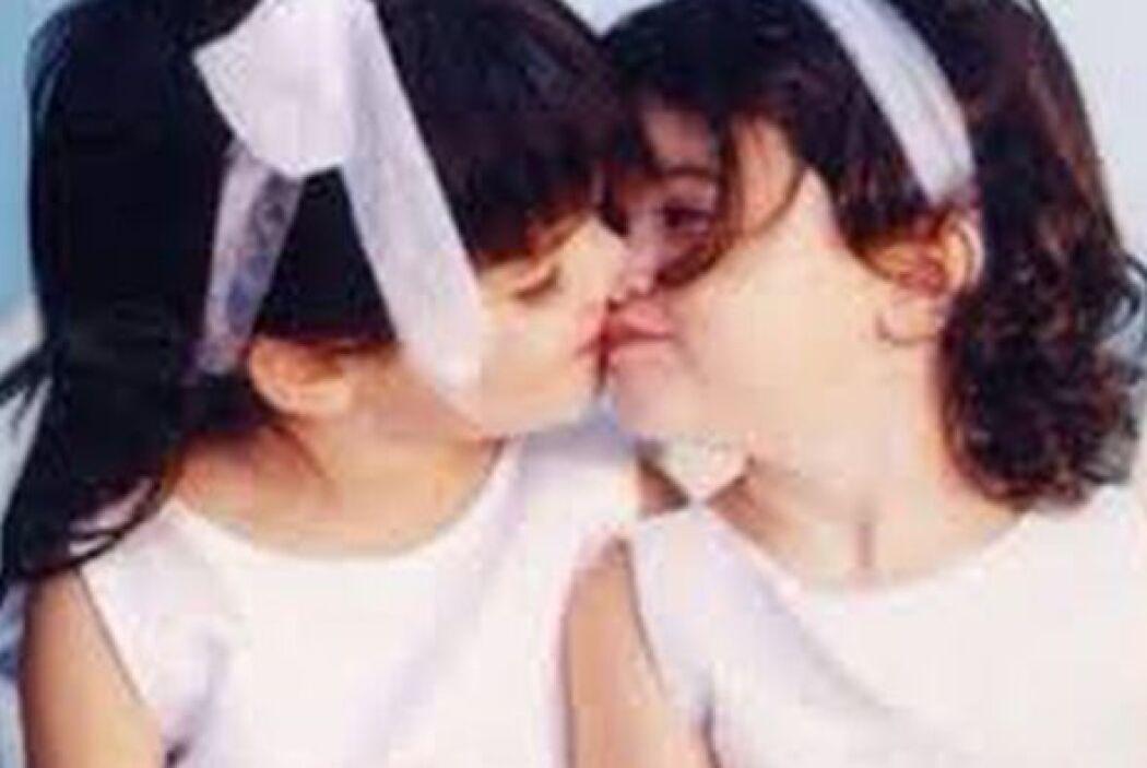 Las dos hermanas compartiendo un besito.