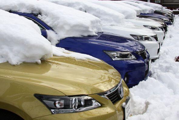 Una venta de automóviles casi sompletamente cubierna de nieve.