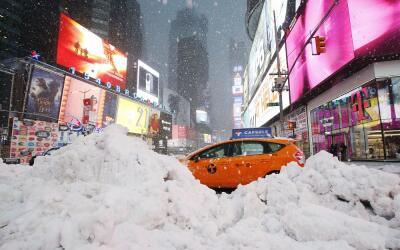 Un taxi pasa entre montones de nieve por Times Square. en Nueva York.