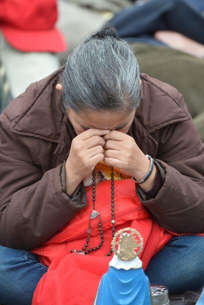 Una mujer reza el santo Rosario previo a la ceremonia de canonización. F...