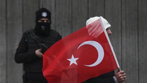 Un hombre con una bandera turca pasa por delante de un policía que custo...