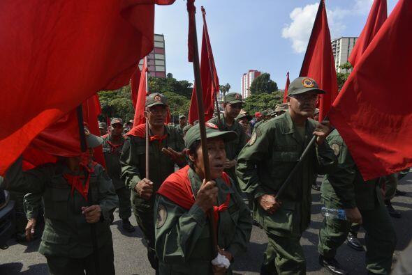 Luciendo el color rojo que identifica al chavismo y afiches o camisetas...