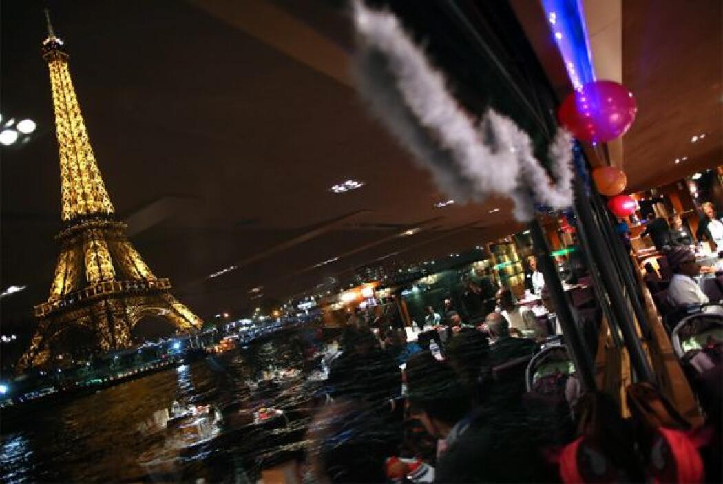 La Torre Eiffel es vista desde un barco en el río Sena en París, por per...