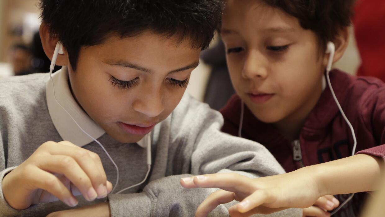 Niños jugando con una tablet durante la Hora del Código.