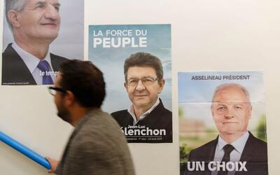 Un votante pasa frente a los carteles electorales de tres de los once ca...