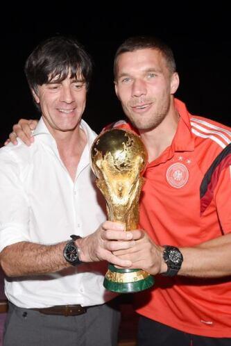 El técnico Joachim Löw junto a Lukas Podolski con el trofeo.