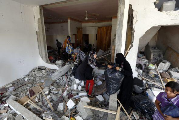 Mujeres palestinas encuentran en ruinas su casa, al norte de Gaza.