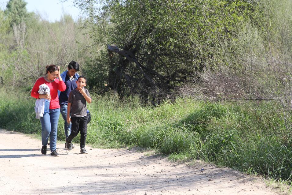 Tres migrantes venidos de El Salvador caminan mientras se le acerca una...