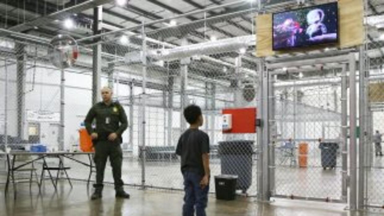 Un niño migrante indocumentado mira una película en un centro de detenci...