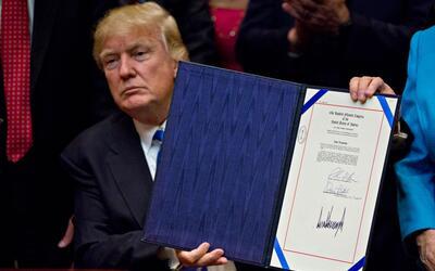 Donald Trump muestra la H.J. Res. 57, la ley que deroga reglas de respon...